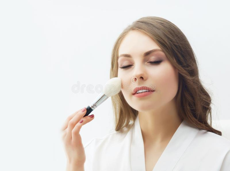 Beauty portrait of young and attractive girl. Make-up and cosmetics concept. Young and beautiful girl preparing makeup. Bride doing make-up near the mirror stock photos