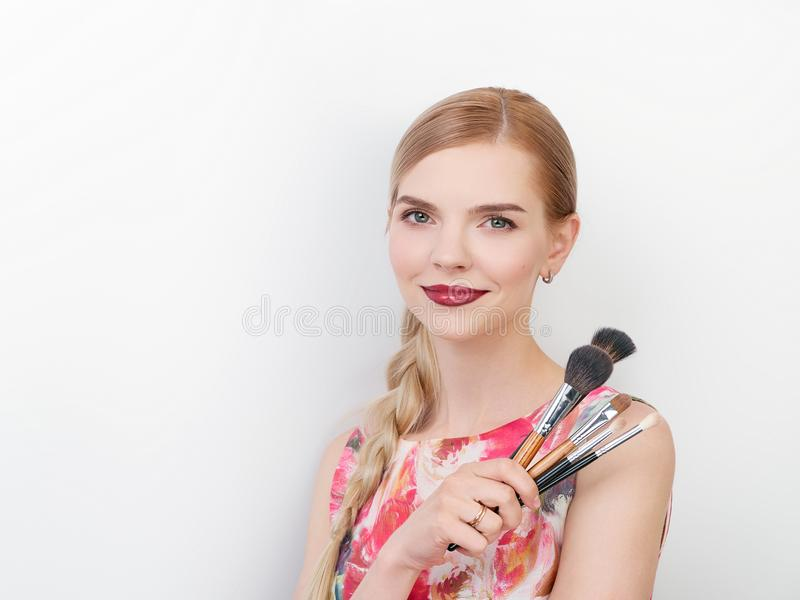 Beauty portrait of young beautiful cheerful young fresh looking make up artist lady with bright trendy make up long blond healthy. Beauty portrait of young royalty free stock photography