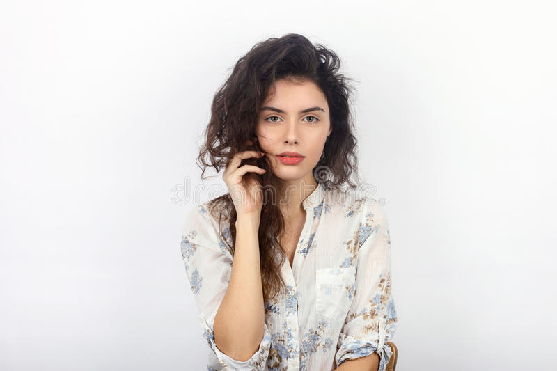 Beauty portrait of young beautiful cheerful young fresh looking woman with long brown healthy curly hair. Concept on white backgro royalty free stock photography