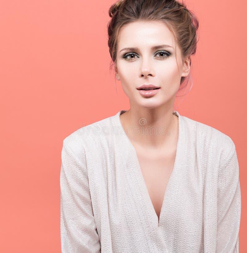 Beauty portrait of young beautiful woman on light orange background stock photo