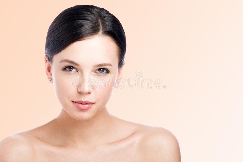 Beauty portrait of a young beautiful woman with a light smile. Nude makeup and perfect skin stock photography