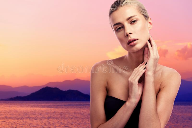 Beauty portrait of a young beautiful woman at sunset. Black swimsuit and blonde hair. Mountains and sea in the background stock photo