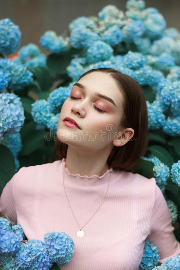 Beauty portrait of young brunette woman with bright makeup, dressed in pink t-shirt standing among blue flowers stock photo