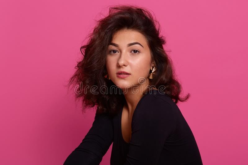 Beauty portrait of young Caucasian girl with dark wavy. Girl posing over rosy background, looking at camera, having confident royalty free stock photos