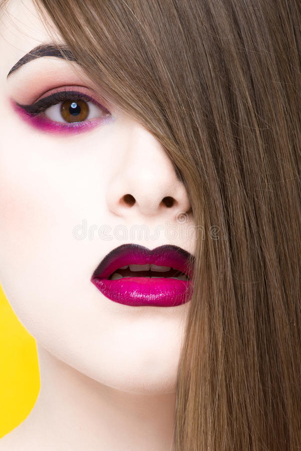 Beauty portrait of young white girl with creative makeup and hair isolated on yellow background. stock image