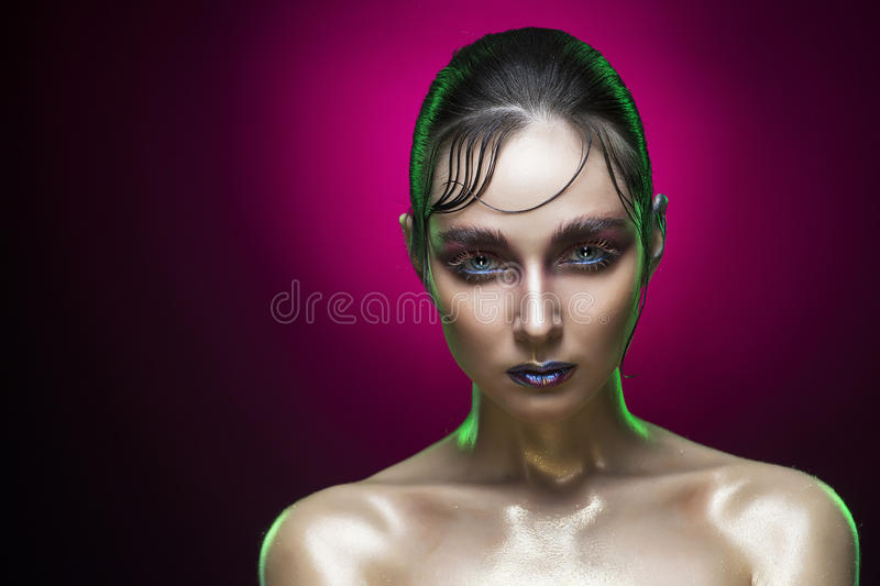 Beauty portrait of the young woman with an accurate hairstyle and vanguard wet shine make-up on a red gradient background royalty free stock image
