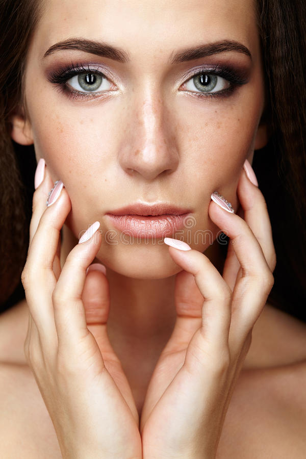 Beauty portrait of young woman touching face with fingers. Brunette girl with long hair and day female makeup.  royalty free stock photos