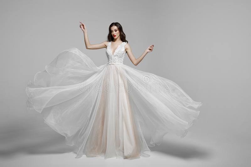 Beauty portrait of a young woman in wedding fashion long dress in waving flying fabric, cloth fluttering in wind. royalty free stock photo