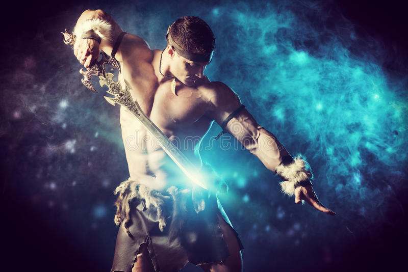 Beauty of power. Portrait of a handsome muscular ancient warrior with a sword royalty free stock photo
