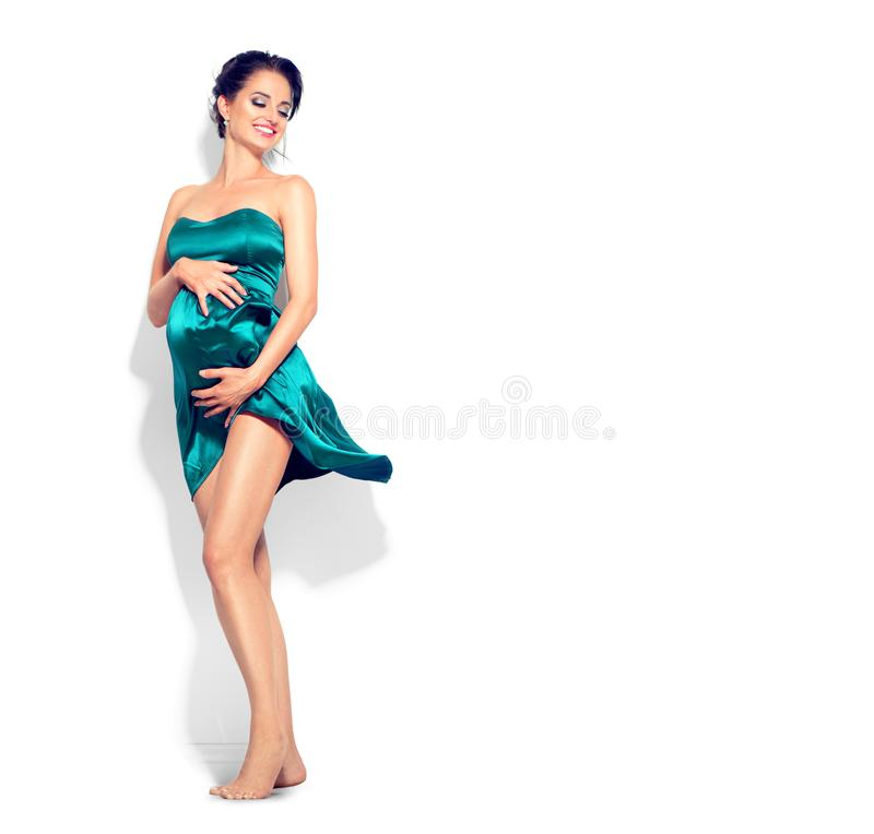 Beauty pregnant woman in fashion fluttering green silk dress posing in studio royalty free stock images