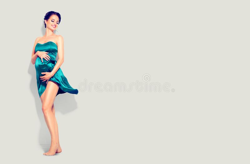 Beauty pregnant woman in fashion fluttering green silk dress posing in studio stock image