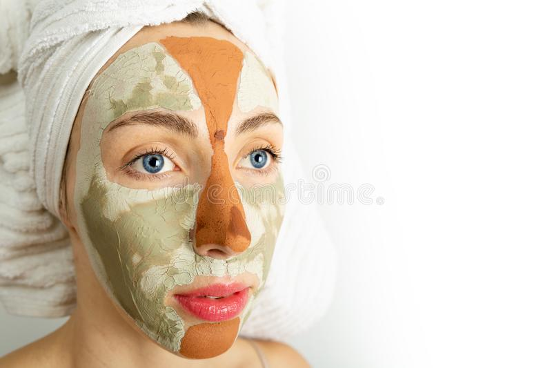 Beauty procedures skin care concept. Young woman applying facial gray and red mud clay mask to her face in bathroom. Woman with stock photo