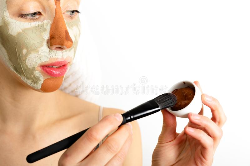 Beauty procedures skin care concept. Young woman applying facial gray and red mud clay mask to her face in bathroom. Woman with. Different masks on her face royalty free stock photos