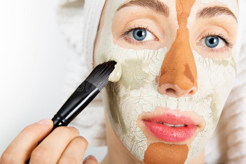 Beauty procedures skin care concept. Young woman applying facial gray and red mud clay mask to her face in bathroom. Woman with. Different masks on her face royalty free stock photography