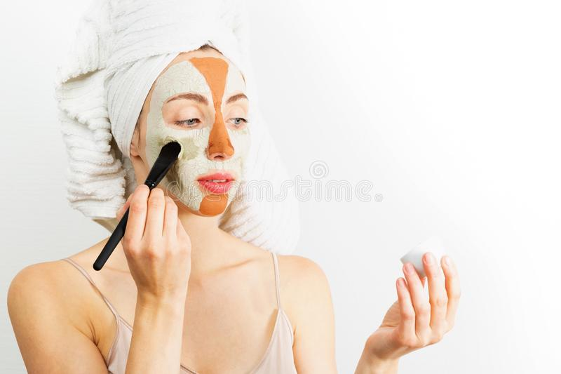 Beauty procedures skin care concept. Young woman applying facial gray and red mud clay mask to her face in bathroom. Woman with. Different masks on her face royalty free stock image