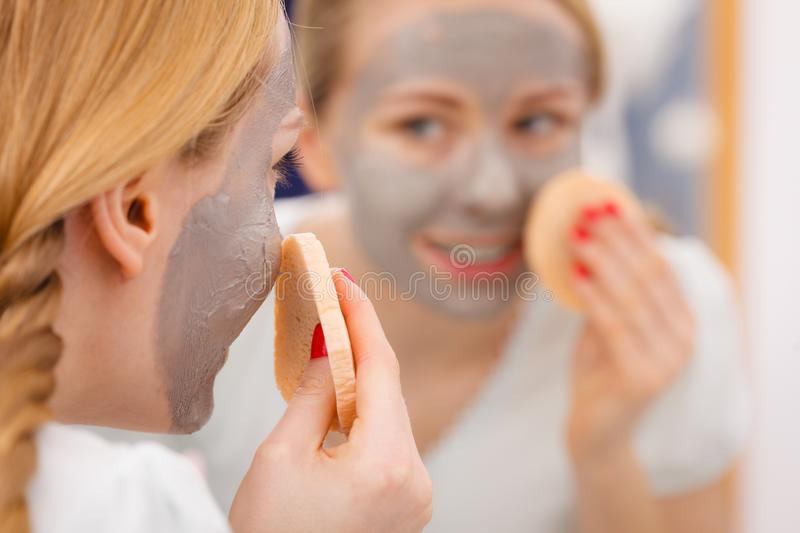 Woman removing mud facial mask with sponge. Beauty procedures spa and skin care concept. Young woman looking in mirror, removing facial clay mud mask with sponge royalty free stock photography