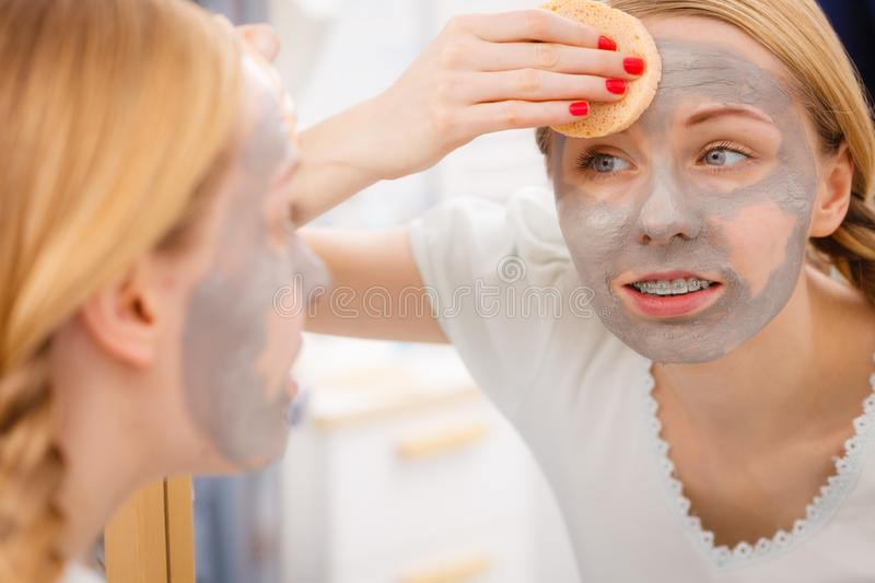 Woman removing mud facial mask with sponge. Beauty procedures spa and skin care concept. Young woman looking in mirror, removing facial clay mud mask with sponge stock image