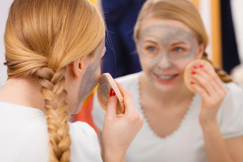 Woman removing mud facial mask with sponge. Beauty procedures spa and skin care concept. Young woman looking in mirror, removing facial clay mud mask with sponge royalty free stock images