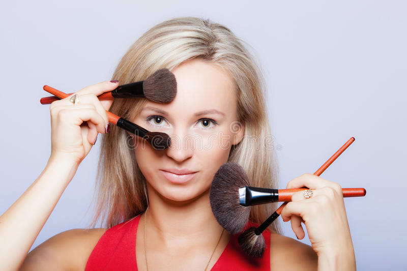Beauty procedures, woman holds make-up brushes near face. stock image