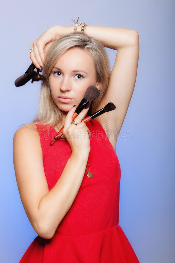 Beauty procedures, woman holds make-up brushes near face. royalty free stock photos