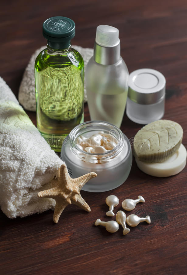 Beauty products. Cosmetics for face and body - toner, lotion, cream, capsules with rejuvenating facial oil, handmade soap,towel. On dark wooden surface stock photography