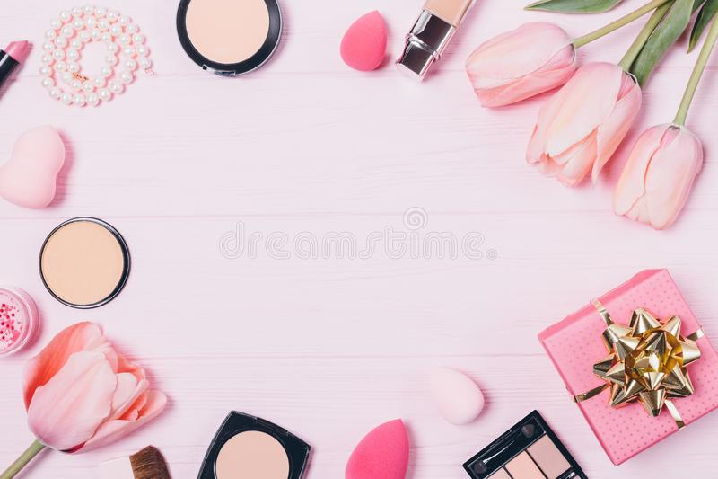 Beauty products and fresh tulip flowers. On pink table, top view. Flat layout of decorative women\'s cosmetics and accessories on wooden background with free stock image