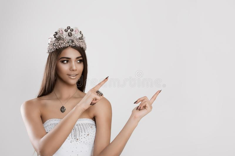 Beauty queen pointing with her fingers to her left to blank empty copy space royalty free stock photography