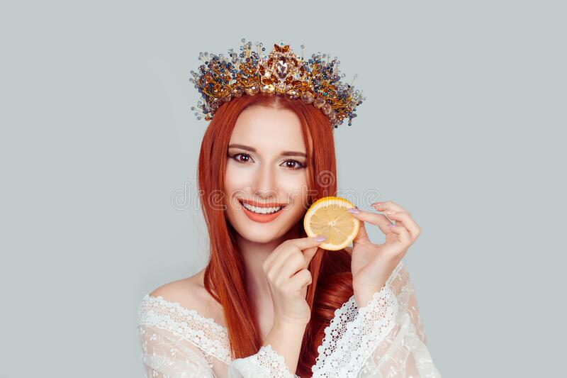 Beauty queen and Vitamin C. A young woman holding slice of orange smiling pretty woman with crystal crown on head isolated on royalty free stock photos
