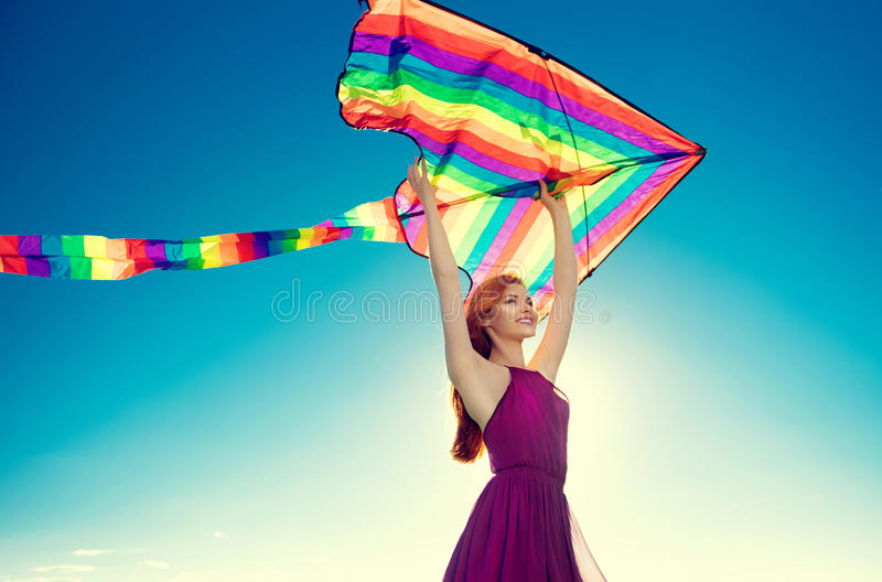 Beauty redhead girl with flying colorful kite over blue sky royalty free stock photography