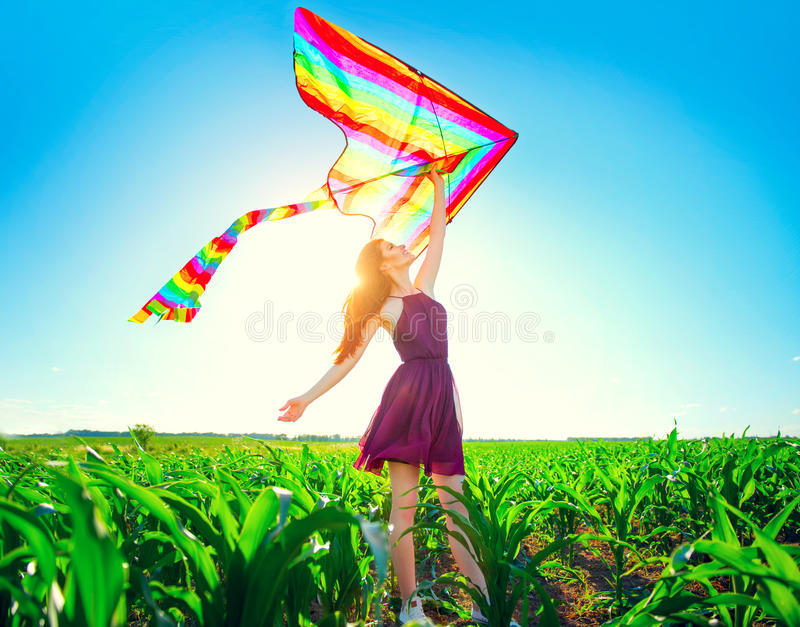 Beauty redhead girl with flying colorful kite stock photo