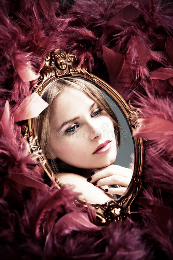 Beauty reflection. Beautiful young woman reflection in mirror surrounded by plumage stock photography