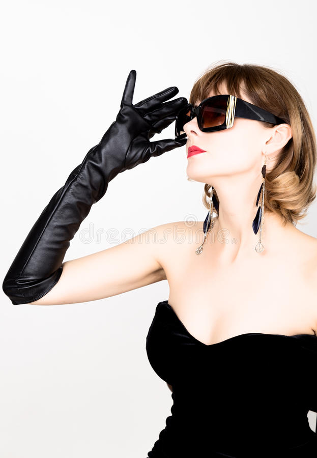 Beauty retro female model with professional makeup in a long leather gloves, holding over size sunglasses. Beauty retro female model with professional makeup in royalty free stock photo