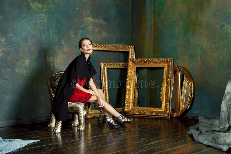 Beauty rich brunette woman in luxury interior near empty frames, wearing fashion clothes, lifestyle pretty real people. Concept closeup royalty free stock images