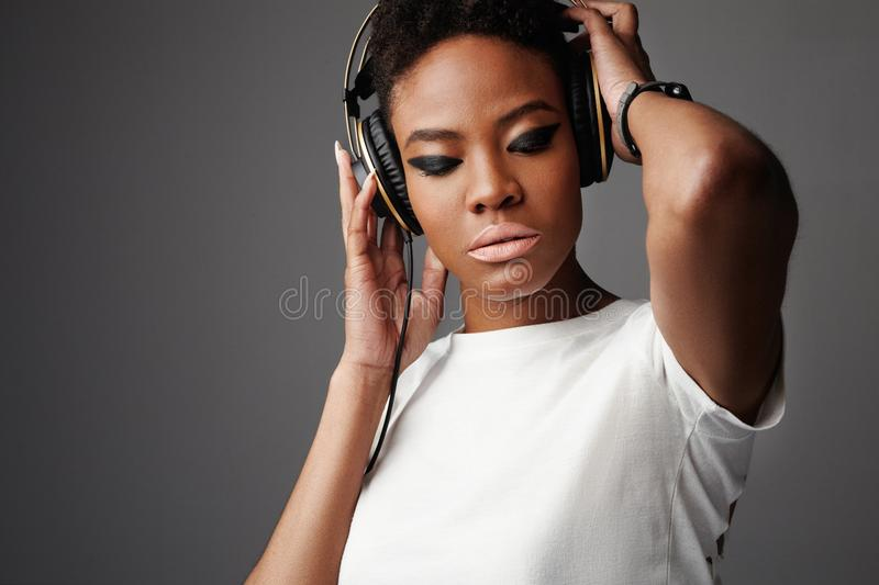 Beauty rock style black woman with big earphones stock image