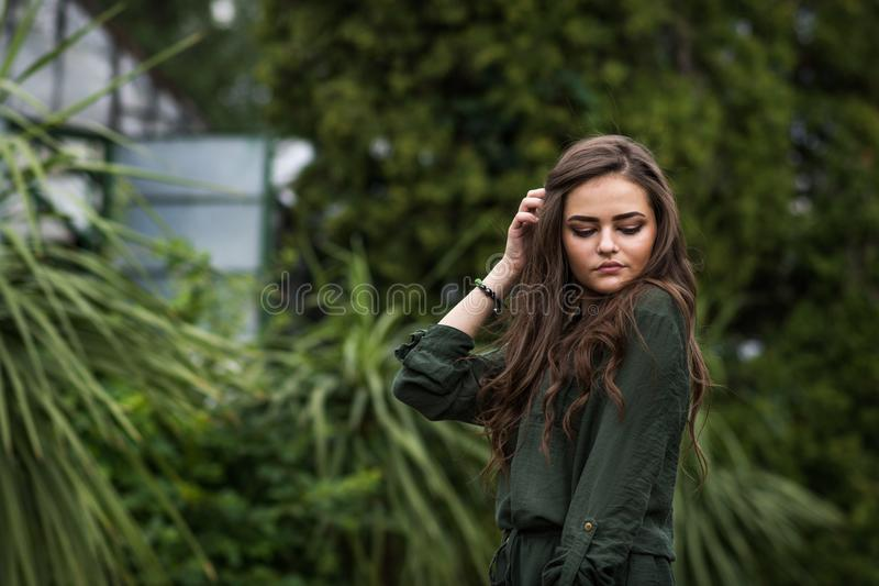 Beauty Romantic Girl Outdoor. Beautiful Teenage Model Dressed in Fashionable Green Dress Posing Outdoors in park. stock image