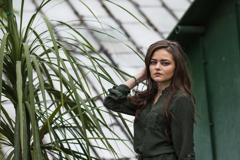 Beauty romantic girl outdoor. Beautiful teenage model dressed in fashionable green dress posing outdoors in park. Toned in warm co royalty free stock images