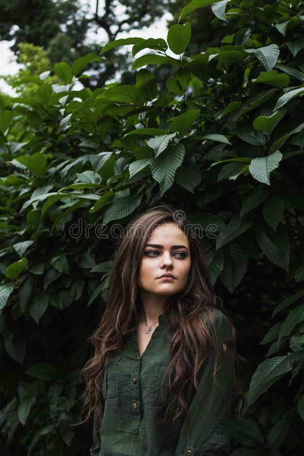 Beauty romantic girl outdoor. Beautiful teenage model dressed in fashionable green dress posing outdoors in park. Toned in warm co royalty free stock photography