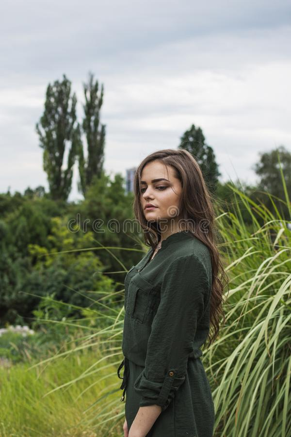 Beauty Romantic Girl Outdoor. Beautiful Teenage Model Dressed in Fashionable Green Dress Posing Outdoors in park. Toned in warm co royalty free stock photo