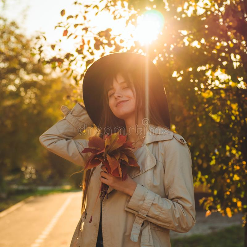 Beauty Romantic Girl Outdoors enjoying nature holding leaves in hands. Beautiful autumn model with waving glow hair. Sun light stock image
