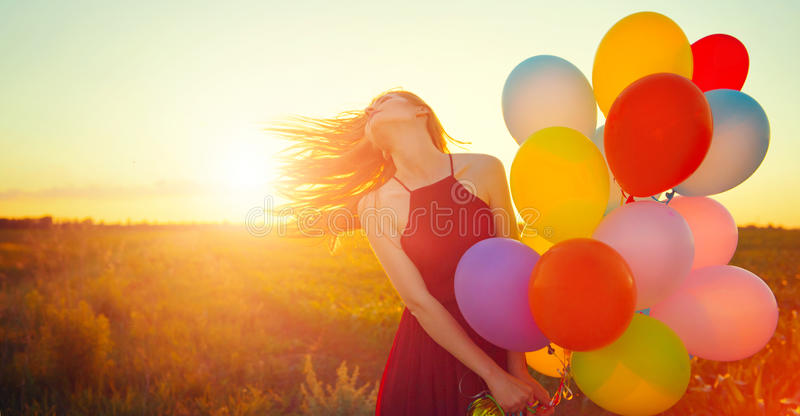 Beauty romantic girl on summer field with colorful air balloons royalty free stock photography