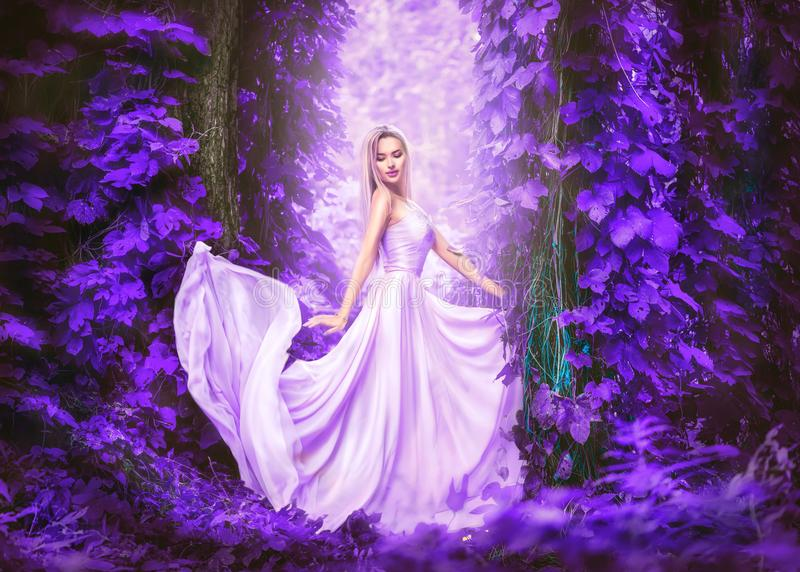 Beauty romantic young woman in long chiffon dress with gown posing in fantasy misty forest. Beautiful happy bride model girl royalty free stock images