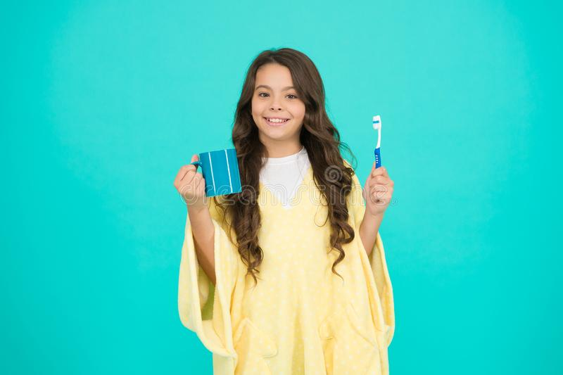 Beauty routine. Cleaning teeth. Child in pajamas hold mug and toothbrush. Oral hygiene. Taking care of her smile royalty free stock images