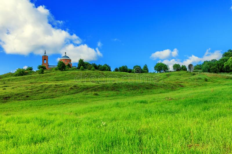 The beauty of Russian fields in the summer. Hills with green grass on the background of the old Russian Church.  royalty free stock photos