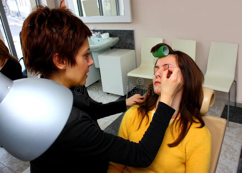 Beauty salon. A beautician plucking women eyebrows at a beauty salon royalty free stock images