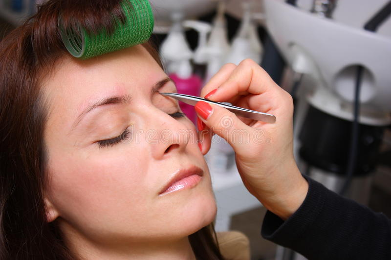 Beauty salon. Plucking woman eyebrows with tweezers at a beauty salon close up shot royalty free stock image