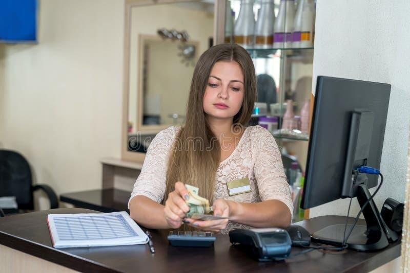 Beauty salon administrator translates dollars . The beauty salon administrator translates dollars royalty free stock images
