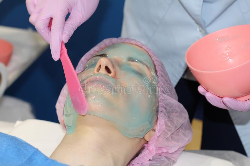 Beautician applies Alginate Peel-Off Powder Mask for the face. In a beauty salon. Beautician applies Alginate Peel-Off Powder Mask for the face. Skin care royalty free stock image