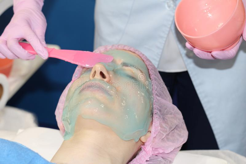 Beautician applies Alginate Peel-Off Powder Mask for the face. In a beauty salon. Beautician applies Alginate Peel-Off Powder Mask for the face. Skin care stock image