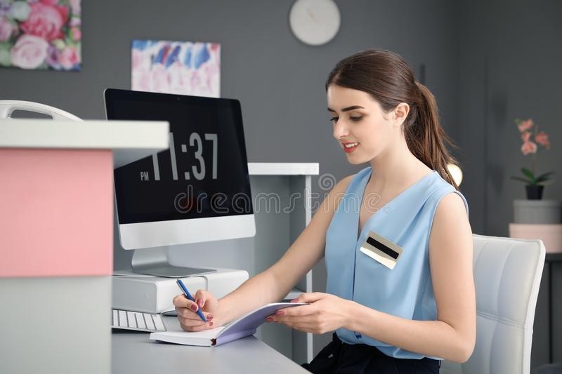 Beauty salon receptionist with notebook. At desk royalty free stock images