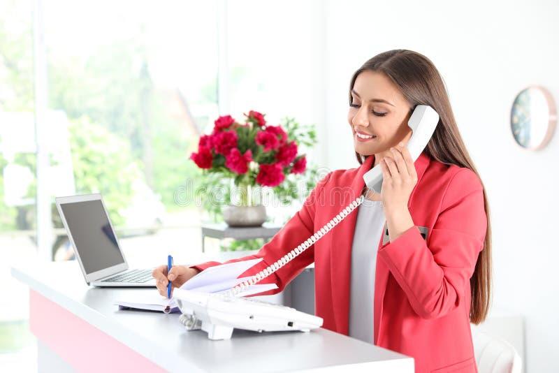 Beauty salon receptionist talking on phone royalty free stock photo